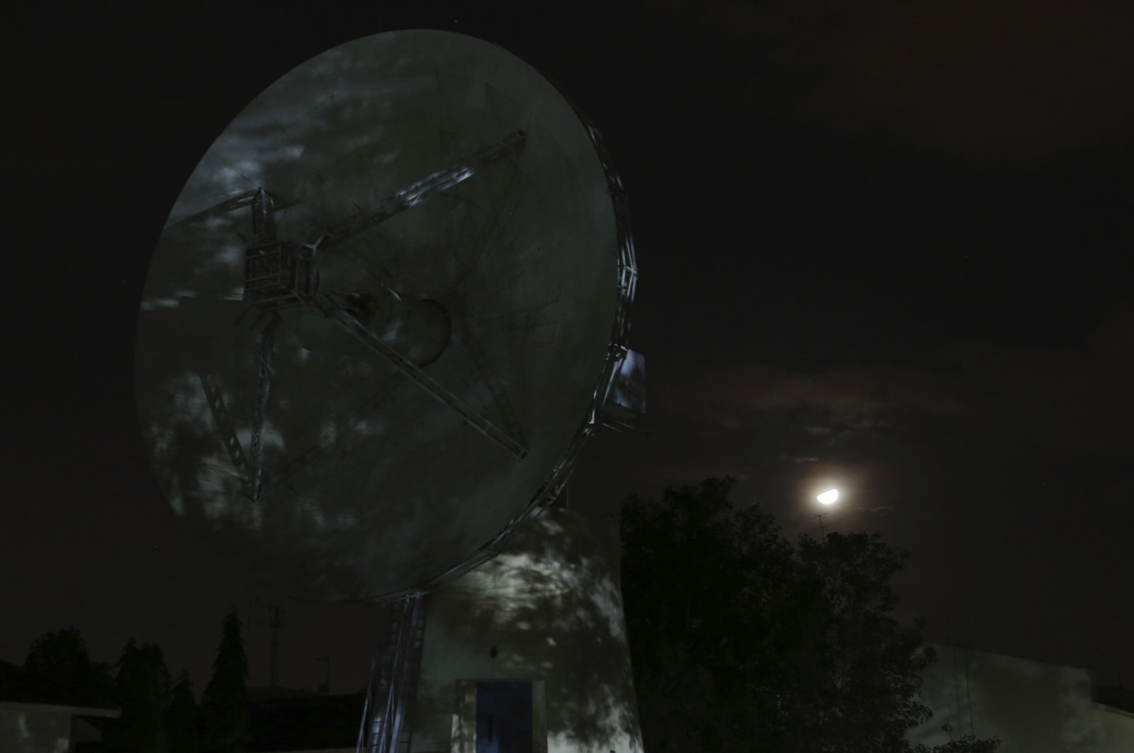 The moon is seen behind a tracking antenna at Indian Space Research Organization's Telemetry, Tracking and Command Network facility in Bangalore, India, late Friday, Sept. 6, 2019. India's space agency said it lost touch Saturday with its Vikram lunar lander as it aimed to land on the south pole of the moon and deploy a rover to search for signs of water. (AP Photo/Aijaz Rahi)